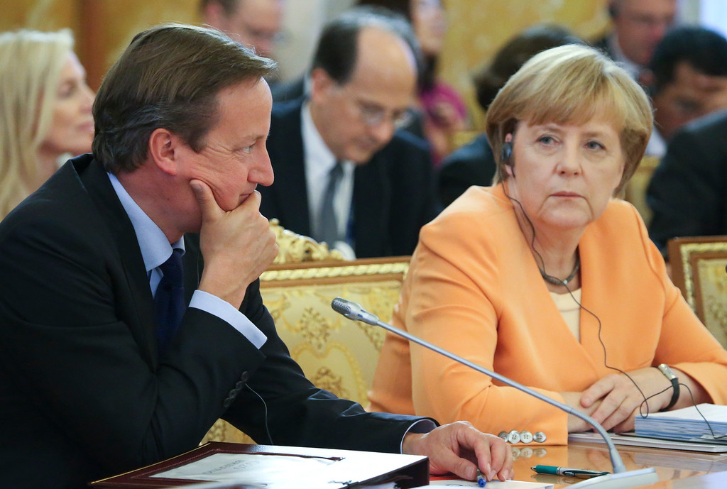 . British Prime Minister David Cameron, left, and Germany\'s Chancellor Angela Merkel listen during a round table meeting at the G-20 summit in St. Petersburg, Russia on Thursday, Sept. 5, 2013. (AP Photo/Sergei Karpukhin, Pool)