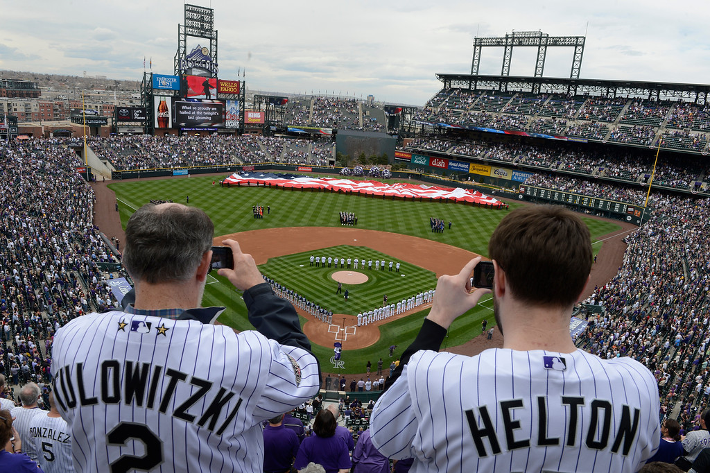 . John Schwartz, left, and his son, Scott, both from Denver, stand for the National Anthem before the start of the game. They have been season ticket holders since the first Rockies season in 1993. (Photo by Andy Cross/The Denver Post)