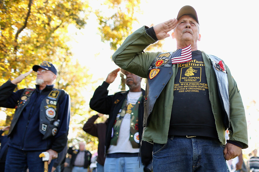 """. Vietnam War veteran Jim Hauser of Riva, Maryland salutes with fellow veterans during a Veterans Day event at the Vietnam Veterans Memorial on the National Mall November 11, 2013 in Washington, DC. Thousands of people gathered at \""""The Wall\"""" to pay respects and honor the men and women who served during the Vietnam War.  (Photo by Chip Somodevilla/Getty Images)"""