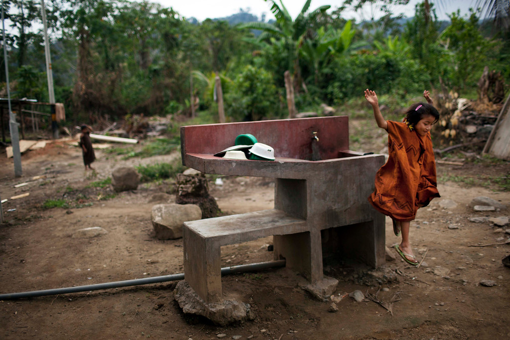 . In this Oct. 1, 2013 photo, an Ashaninka Indian girl jumps off a communal sink that was provided by the government, in Kimkibiri Baja, Pichari district, Peru. One of 350 Ashaninka communities, Kimkibiri Baja lies in the Apurimac river valley, the No. 1 coca-producing valley in the world. The government is now boosting its military footprint in the valley in a bid to fight Shining Path remnants and the drug traffickers they protect. (AP Photo/Rodrigo Abd)