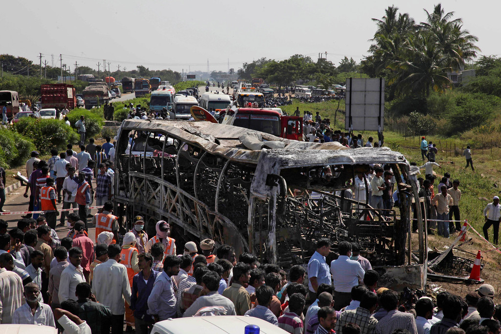 . Rescuers and others gather near the debris after a bus crashed into a highway barrier and erupted in flames at Mehabubnagar in southern Andhra Pradesh state, India, Wednesday, Oct. 30, 2013. According to officials many of the passengers were burned alive in the accident that happened early Wednesday. (AP Photo/Mahesh Kumar A.)