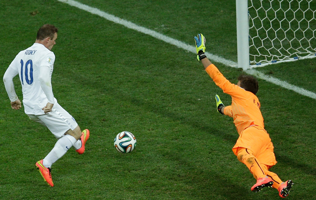 . England\'s Wayne Rooney, left, scores his side\'s first goal past Uruguay\'s goalkeeper Fernando Muslera during the group D World Cup soccer match between Uruguay and England at the Itaquerao Stadium in Sao Paulo, Brazil, Thursday, June 19, 2014.  (AP Photo/Michael Sohn)