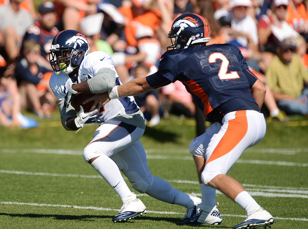 . CENTENNIAL, CO. - August 10: Zac Dyser of Denver Broncos (2) hands the ball to C.J. Anderson of Denver Broncos (39) during the training camp at Dove Valley. Centennial, Colorado. August 10, 2013. (Photo By Hyoung Chang/The Denver Post)