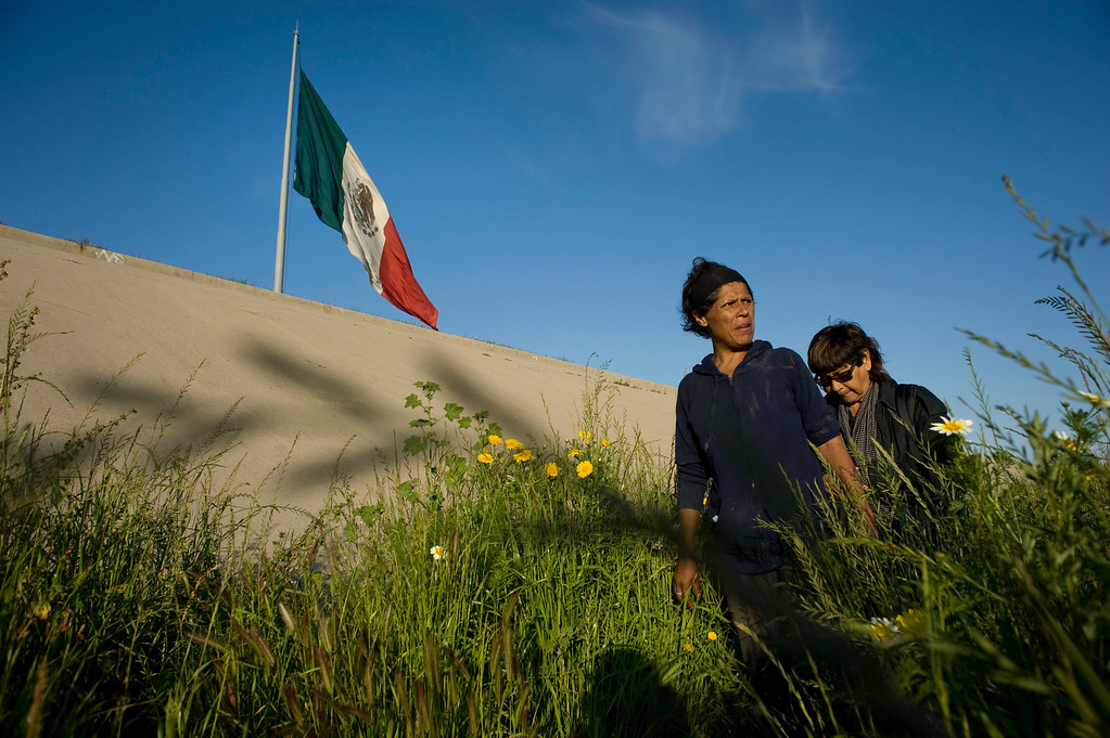 . Marta Gomez (L), 42, walks among plants in the Tijuana River canal, which has become home to hundreds of people deported from the US, in Tijuana, Mexico, 27 March 2013. Gomez was deported three years ago and has been living in the canal. She has nine children who live in the United States. Behind Gomez is Micaela Saucedo, who has a shelter and helps the homeless. Heightened US border security and record numbers of deportations from the US have created a growing population of people who live homeless in Mexican cities that border with the United States. Many had lived for years undocumented in the US and have little or no family and other support in Mexico, and are subject to fall into depression, substance abuse and crime. Tijuana, Mexico, borders on the US city of San Diego, California.  EPA/DAVID MAUNG