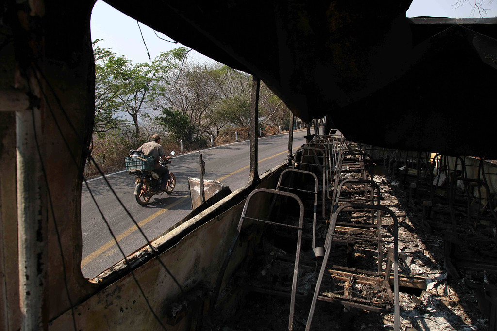 . In this May 20, 2013 photo, a man on a motorcycle drives past the burnt-out hulks of two trucks and a passenger bus, allegedly torched by the Knights Templar drug cartel as a warning to anyone who tries to bring reinforcements, near the town of Buenavista, Mexico. A drug cartel that takes its name from an ancient monastic order has set fire to lumber yards, packing plants and passenger buses in a medieval-like reign of terror. (AP Photo/Marco Ugarte)