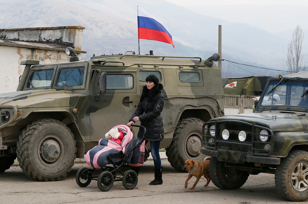 ". A woman walks with her baby in front of Russian \'GAZ Tigr\' infantry mobility vehicle outside the territory of Ukrainian military unit in the village of Perevalnoye, outside Simferopol, Ukraine, 12 March 2014. Crimea\'s secessionist authorities said on 12 March that they have partially closed the region\'s airspace to ""keep out provocateurs\"" in the run-up to the March 16 referendum about joining Russia.  EPA/YURI KOCHETKOV"