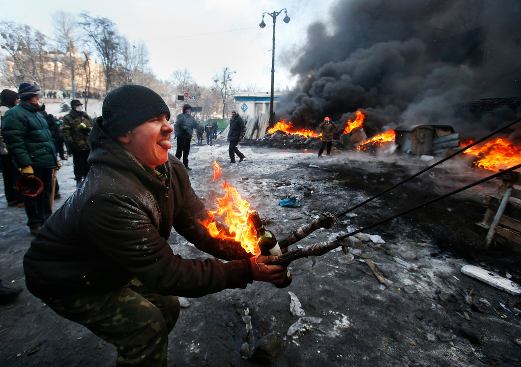 . Protesters use a large slingshot to hurl a Molotov cocktail at police in central Kiev, Ukraine, Thursday Jan. 23, 2014. Thick black smoke from burning tires engulfed parts of downtown Kiev as an ultimatum issued by the opposition to the president to call early election or face street rage was set to expire with no sign of a compromise on Thursday. (AP Photo/Sergei Grits)