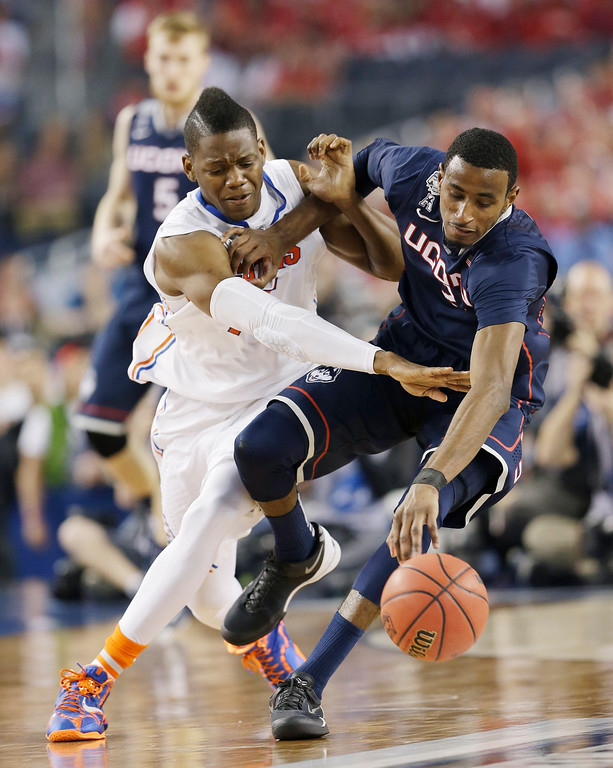 . Florida forward Will Yeguete (15) reaches in against Connecticut forward DeAndre Daniels (2) during the second half of the NCAA Final Four tournament college basketball semifinal game Saturday, April 5, 2014, in Arlington, Texas. (AP Photo/David J. Phillip)