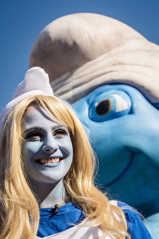 """. A Smurf-ambassador smiles as she walks by a giant inflatable Smurf during the Global Smurfs Day gathering in Brussels, Saturday June 22, 2013. The celebration honors Smurfs creator Pierre \'Peyo\' Culliford\'s June 25 birthday and the opening of movie  \""""The Smurfs 2\"""" on July 31. (AP Photo/Geert Vanden Wijngaert)"""