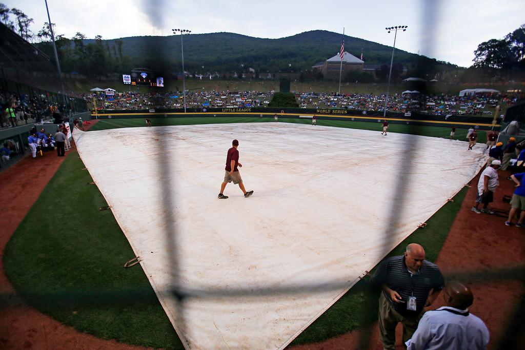 . The grounds crew at Lamade Stadium cover the field, delaying an elimination baseball game between Chicago and Philadelphia at the Little League World Series tournament in South Williamsport, Pa., Thursday, Aug. 21, 2014. (AP Photo/Gene J. Puskar)