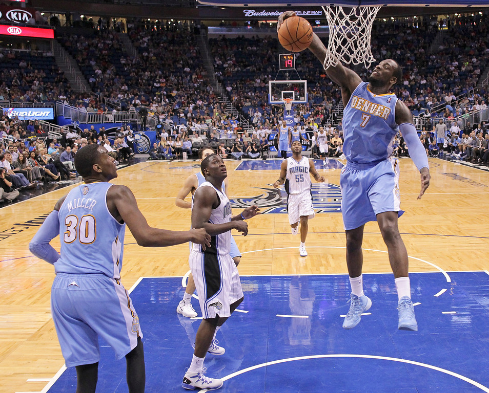 . Denver Nuggets\'s J.J. Hickson (7) grabs an offensive rebound before going up for shot in front of Orlando Magic\'s Victor Oladipo, center, as Denver\'s Quincy Miller (30) looks on during the second half of an NBA basketball game in Orlando, Fla., Wednesday, March 12, 2014. Denver won 120-112. (AP Photo/John Raoux)