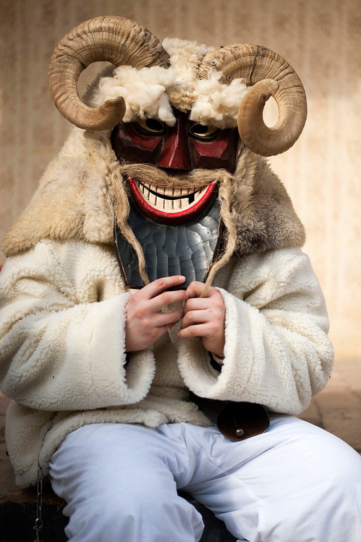 . A young reveler wears a sheep-fur costume and wooden mask as he with others gets ready for the traditional carnival parade in the yard of a house in Mohacs, 189 kms south of Budapest, Hungary, 27 February 2014. The carnival parade of the so-called busos, wearing costumes and wooden masks, using various noisy wooden rattlers is traditionally held on the seventh weekend before Easter to drive away winter, and is a revival of a legend, which says that ethnic Croats ambushed the Osmanli Turkish troops, who escaped in panic seeing the terrifying figures during the Turkish occupation of Hungary.  EPA/TAMAS SOKI HUNGARY OUT