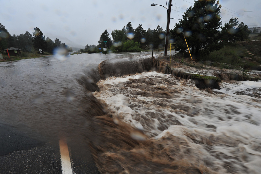 . The Fish Creek runs over its namesake road at Brodie Avenue on Thursday morning, September 12, 2013. Waters rose trapping residents in their neighborhoods as rain continued.  Walt Hester/Estes Park Trail-Gazette