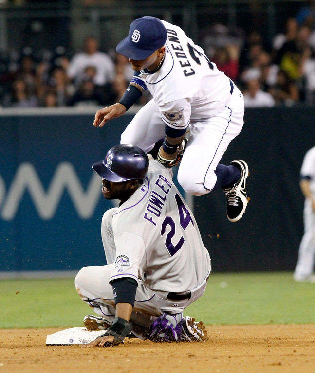. Colorado Rockies\' Dexter Fowler slides in safe under the tag by San Diego Padres shortstop Ronny Cedeno during the fifth inning of the baseball game on Friday, Sept. 6, 2013, in San Diego. (AP Photo/Don Boomer)