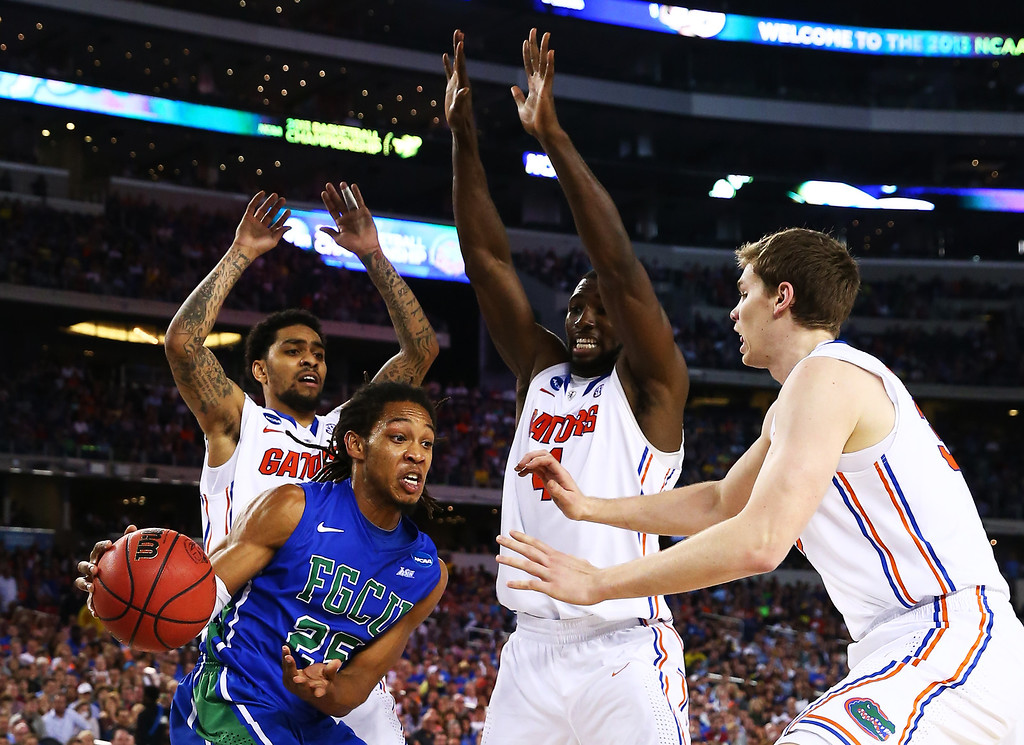 . ARLINGTON, TX - MARCH 29:  Sherwood Brown #25 of the Florida Gulf Coast Eagles passes around Erik Murphy #33 and Patric Young #4 of the Florida Gators in the second half during the South Regional Semifinal round of the 2013 NCAA Men\'s Basketball Tournament at Dallas Cowboys Stadium on March 29, 2013 in Arlington, Texas.  (Photo by Tom Pennington/Getty Images)