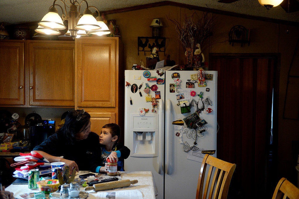 . MILLIKEN, CO - DECEMBER 18: Martha Gutierrez, manager, holds her grandson, Angelo Castillo, 3, at the Evergreen Mobile Home Park. Residents of the mobile home park say that the city of Milliken has not done enough to assist in the rebuilding of the 33-unit residential sub division that was struck hard by recent floods that ravaged much of northern Colorado. (Photo by AAron Ontiveroz/The Denver Post)