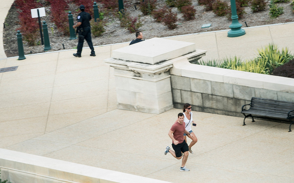". People run for cover as police converge to the site of a shooting October 3, 2013 on Capitol Hill in Washington, DC. The US Capitol was placed on security lockdown Thursday after shots were fired outside the complex, senators said. ""Shots fired outside the Capitol. We are in temporary lock down,\"" Senator Claire McCaskill said on Twitter. Police were seen running within the Capitol building and outside as vehicles swarmed to the scene. AFP PHOTO / Brendan SMIALOWSKI/AFP/Getty Images"