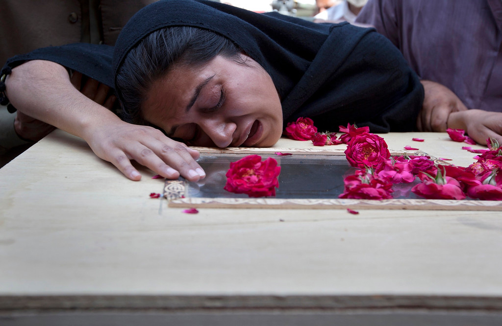 . Ayesha Ishaque, sister of Mohammad Saud Ishaque who was killed in a Boeing 737 airliner crash, cries over his casket at the Pakistan Institute of Medical Sciences hospital (PIMS) in Islamabad April 21, 2012. The Pakistani airliner with 127 people on board crashed in bad weather as it came in to land in Islamabad on Friday, scattering wreckage and leaving no sign of survivors. The Boeing 737, operated by local airline Bhoja Air, was flying to the capital from Pakistan\'s biggest city and business hub Karachi. REUTERS/Rebecca Conway