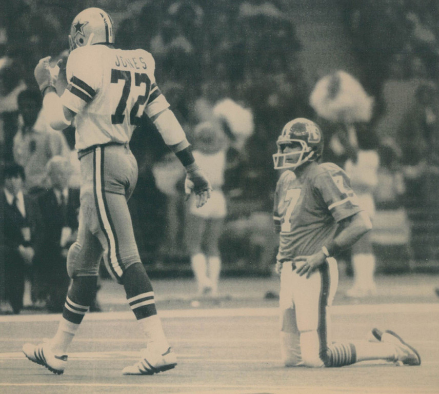 """. The Cowboys defensive team dominated most of Super Bowl XII, forcing 8 turnovers and allowing only 8 pass completions by the Broncos for just 61 yards. Two of those interceptions led to 10 first-quarter points. Denver lost 27-10.  Too Tall Strikes Again--Denver quarterback Craig Morton rests briefly on his knees after being sacked by Dallas defensive end Ed \""""Too Tall\' Jones (72) who walks away following the play. The Cowboys defense got to Morton several times during their Super Bowl XII meeting. 1978  Denver Post"""