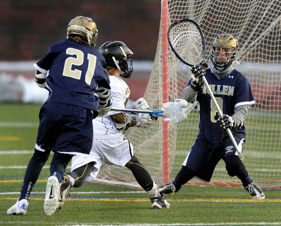 . LITTLETON, CO. - APRIL 10: Mullen defenseman Troy Echer (21) catches Warriors middie Brian Wilson (22) from behind as he challenged goalie Jason Cleary (8) in the first half. The Mullen High School boy\'s lacrosse team defeated Arapahoe 8-7 Wednesday night, April 10, 2013. Photo By Karl Gehring/The Denver Post)