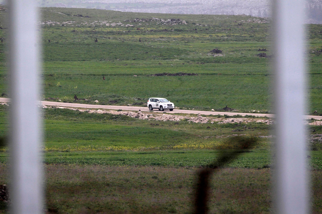 . A United Nations vehicle drives near the Syrian village of Al Jamla, close to the ceasefire line between Israel and Syria, as seen from the Israeli occupied Golan Heights March 5, 2013. Syrian rebels have seized a convoy of U.N. peacekeepers near the Golan Heights and say they will hold them captive until President Bashar al-Assad\'s forces pull back from a rebel-held village which has seen heavy recent fighting. Picture taken March 5, 2013. REUTERS/Baz Ratner