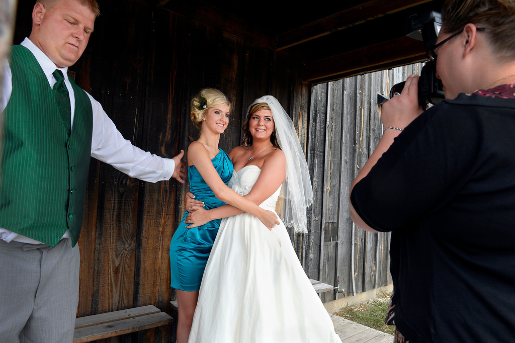 . Nick reaches out to steady sister Mackenzie as she poses with the bride, sister Brittanie. When a doctor told father Steve Gorden Mackenzie wouldn�t walk again, no one knew she heard it. �She just said, �This is what happened to me, this is what I got dealt and this is what I gotta do to get better,� Steve said. (Photo By Craig F. Walker / The Denver Post)