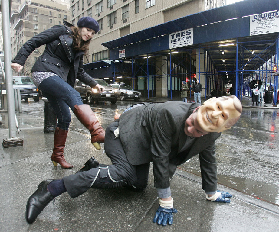 . Amy Brown (L) gives performance artist Mark McGowan, disguised as US President George W. Bush, a kick in the rear end  22 February 2007 in New York. The McGowan-as-Bush character made his way through the streets of Manhattan wearing a sign urging passers by to kick him in the rear.   AFP PHOTO/DON EMMERT