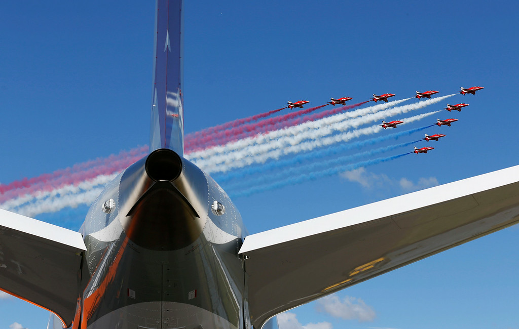 . The Royal Air Force (RAF) Red Arrows aerobatic display team perform a fly past Farnborough Airport to open the International Air Show, Farnborough, England, Monday, July 14, 2014. (AP Photo/Sang Tan)