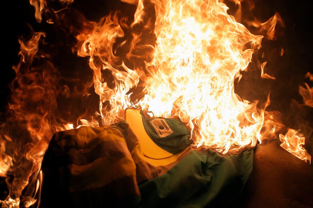 ". Protestors burn a cleaner\'s uniform with a logo reading ""Madrid clean and green\"" during a demonstration against layoffs of cleaners and garbage collectors in Madrid, Spain, Monday, Nov. 4, 2013. Trash collectors in Madrid have started bonfires and set off firecrackers during a noisy protest in one of the Spanish capital\'s main squares as they prepare to start an open-ended strike. Hundreds of street cleaners and garbage collectors who work in the city\'s public parks converged on the Puerta del Sol plaza late Monday. They were due to walk off the job at midnight in a strike called by trade unions to contest the planned layoff of more than 1,000 workers. (AP Photo/Andres Kudacki)"