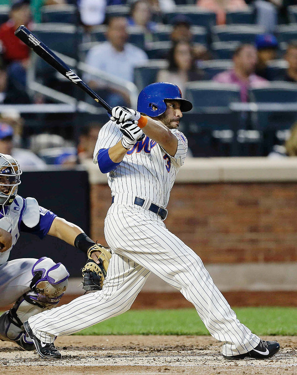 . New York Mets\' Omar Quintanilla follows through on an RBI single during the second inning of a baseball game against the Colorado Rockies on Wednesday, Aug. 7, 2013, in New York. (AP Photo/Frank Franklin II)