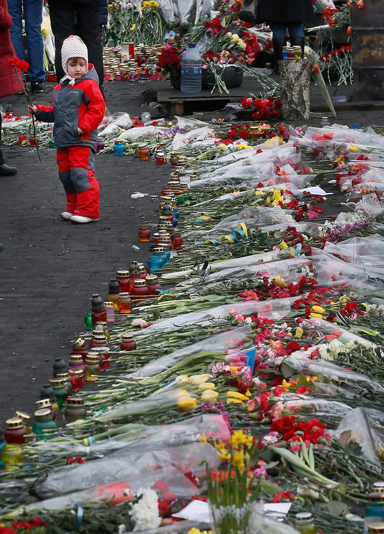 . Ukrainians gather near a long row  of floral truibutes and candles as they remember those killed during the recent violent protests, in Kiev, Ukraine, 26 February 2014.  Former Ukrainian president Viktor Yanukovych had his first public appearance  in Rostov, Russia, since being ousted. He told the there he would fight for his country and insisted he was not overthrown.  EPA/SERGEY DOLZHENKO