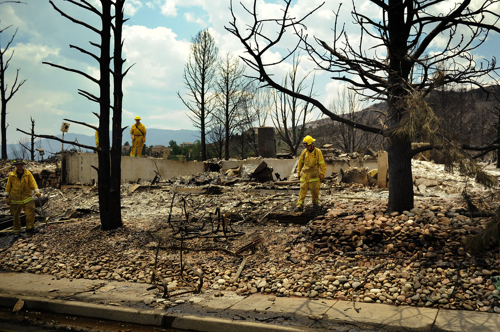 . Firefighters in the Mountain Shadows neighborhood survey the damage after the Waldo Canyon fire swept through in Colorado Springs about three days ago, Friday, June 29, 2012.   Joe Amon, The Denver Post
