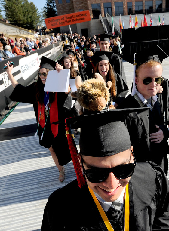 . Favian Castillo comes into Folsom Filed with a Buffalo stuffed animal on his cap  during the 2013 University of Colorado Spring Commencement on Friday in Boulder, Colorado, May 10, 2013. (AP Photo/The Daily Camera, Cliff Grassmick)