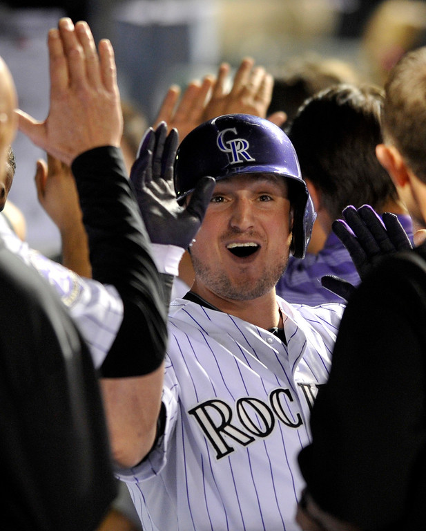 . Colorado Rockies\' Jordan Pacheco (15) is by teammates in the dugout after hitting a grand slam off San Francisco Giants starting pitcher Madison Bumgarner during the fifth inning of a baseball game on Friday, May 17, 2013, in Denver. (AP Photo/Jack Dempsey)