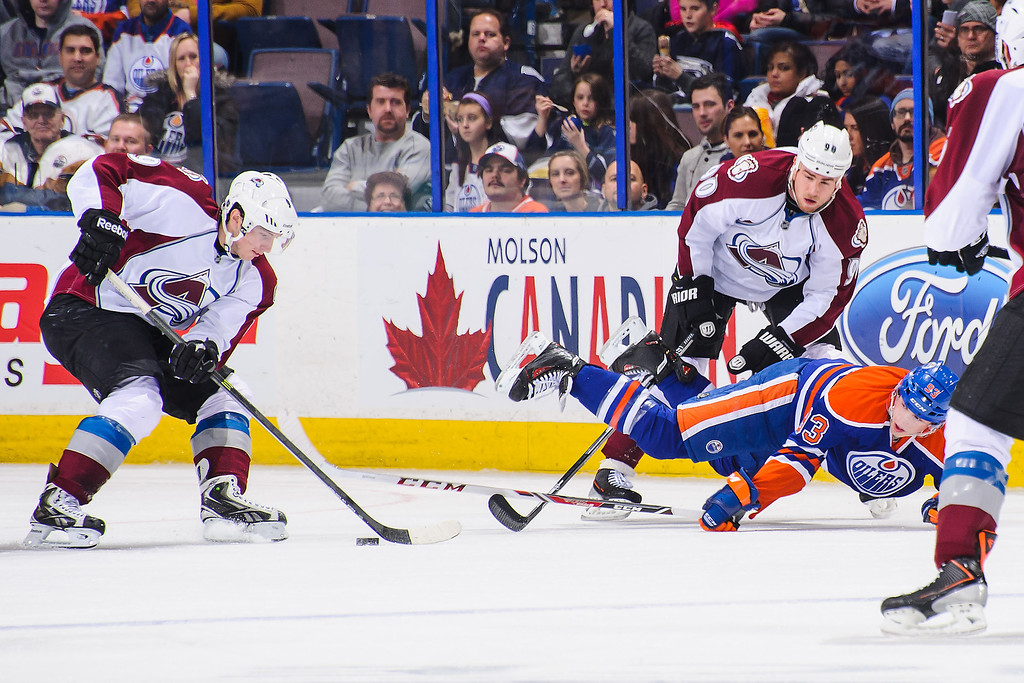 . EDMONTON, AB - DECEMBER 5: Ryan Nugent-Hopkins #93 of the Edmonton Oilers gets knocked off his feet by Ryan O\'Reilly #90 of the Colorado Avalanche as he pursues Matt Duchene #9 during an NHL game at Rexall Place on December 5, 2013 in Edmonton, Alberta, Canada. (Photo by Derek Leung/Getty Images)