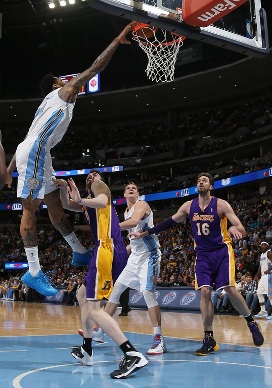 . Denver Nuggets forward Wilson Chandler, left, dunks the ball for a basket over Los Angeles Lakers forward Ryan Kelly, second from left, as Nuggets center Timofey Mozgov, third from left, of Russia, and Lakers center Pau Gasol, of Spain, look on in the fourth quarter of the Nuggets\' 134-126 victory in an NBA basketball game in Denver on Friday, March 7, 2014. (AP Photo/David Zalubowski)