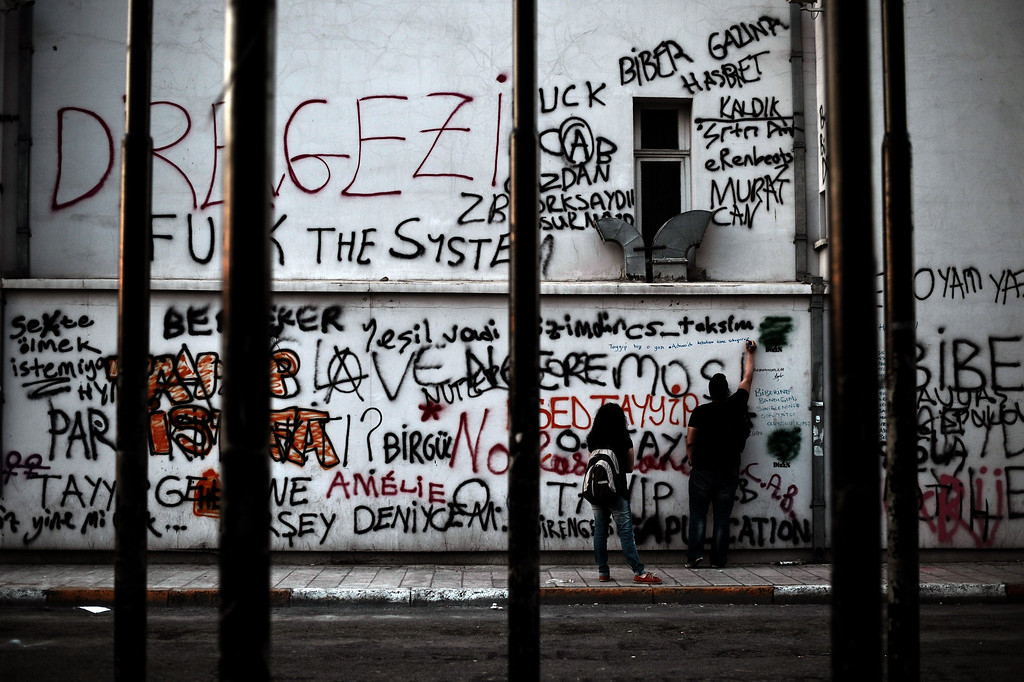 ". A demonstrator writes slogans on  a building painted with graffiti at Taksim square in Istanbul on June 6, 2013. Protests are taking place against the ruling party, police brutality, and the destruction of Taksim park for the sake of a development project. Turkey\'s Islamic-rooted government apologised today to wounded protestors and said it had ""learnt its lesson\"" after days of mass street demonstrations that have posed the biggest challenge to Prime Minister Recep Tayyip Erdogan\'s decade in office. Turkish police had on June 1 begun pulling out of Istanbul\'s iconic Taksim Square, after a second day of violent clashes between protesters and police over a controversial development project. What started as an outcry against a local development project has snowballed into widespread anger against what critics say is the government\'s increasingly conservative and authoritarian agenda.  ARIS MESSINIS/AFP/Getty Images"