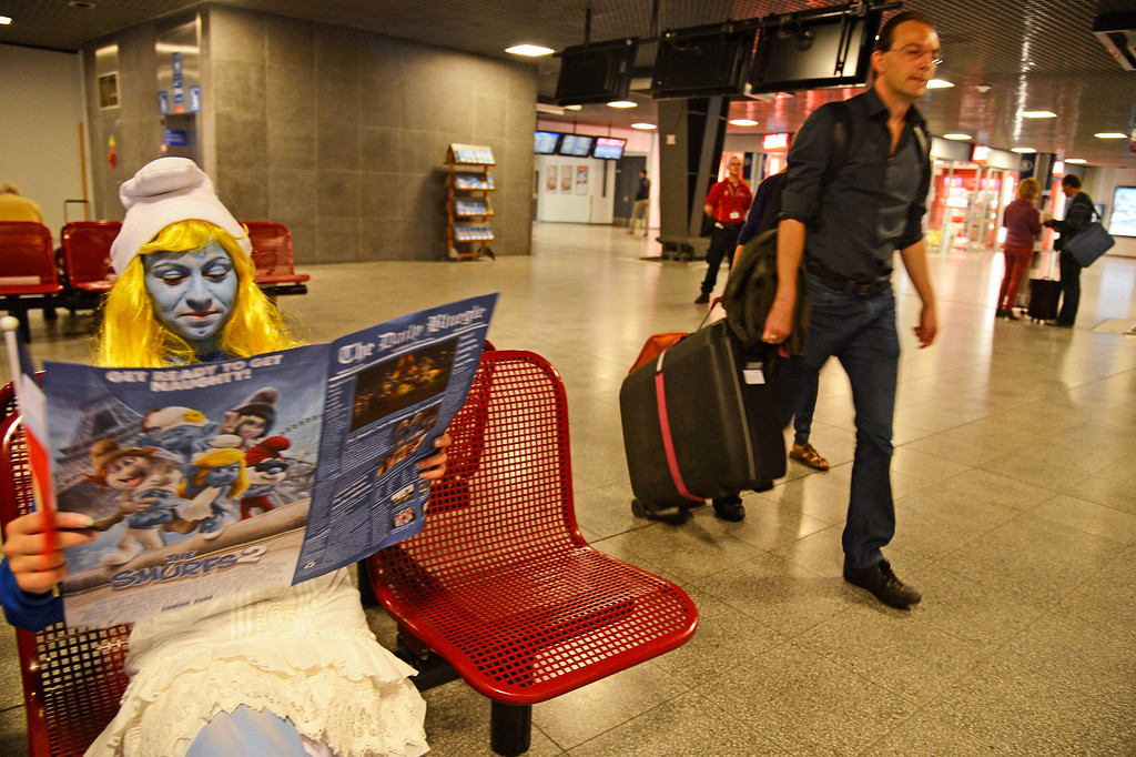 . A Smurf Ambassador reads a special edition of a fake newspaper, designed for the Global Smurfs Day event, in the waiting lounge as Smurf Ambassadors prepare to board a branded high speed train from Brussels to Paris as part of Global Smurfs Day celebrations on June 22, 2013 at Brussels railway station, Belgium.  (Photo by Pascal Le Segretain/Getty Images for Sony Pictures Entertainment)