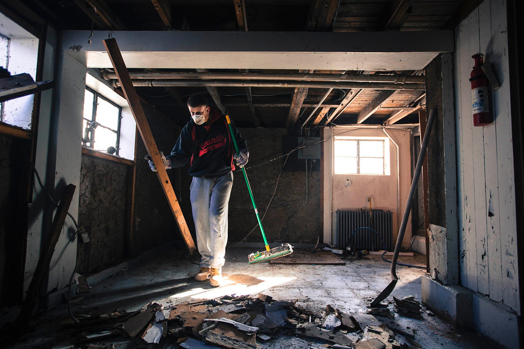 . Sean Martin works to remove interior walls from the home of his friend Lois Kelly to prepare them for replacement, after heavy flood damage during superstorm Sandy in the Staten Island borough neighborhood of Oakwood in New York, November 28, 2012.  REUTERS/Lucas Jackson