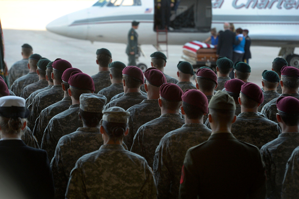 . Green Beret and Airborne stand at attention as family pays their respects to sergeant Liam Nevins, 32, after being brought home from Dover AFB September 30, 2013 at Buckley AFB. Nevins, of Denver, was killed two weekends ago in Afghanistan. (Photo by John Leyba/The Denver Post)