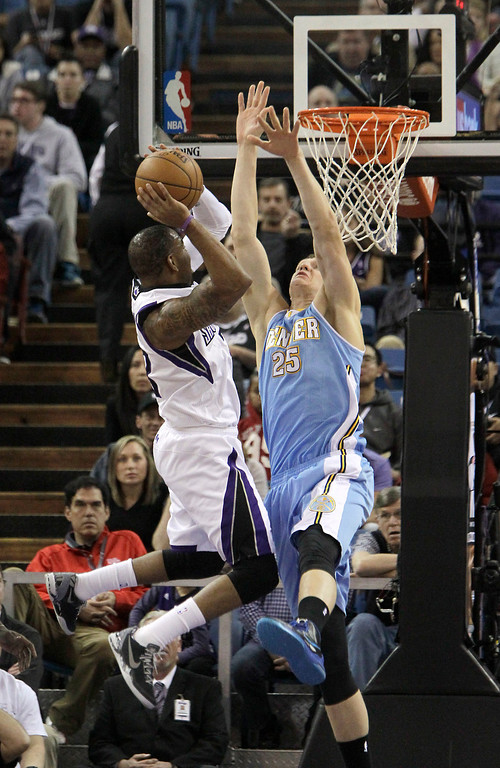 . Sacramento Kings guard Marcus Thornton, left, drives to the basket against Denver Nuggets Timofey Mozgov, of Russia, during the first quarter of an NBA basketball game in Sacramento, Calif., Sunday, Jan. 26, 2014. (AP Photo/Rich Pedroncelli)