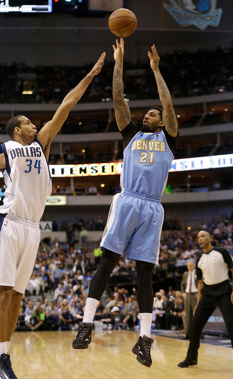 . Denver Nuggets shooting guard Wilson Chandler (21) shoots against Dallas Mavericks center Brandan Wright (34) during the first half of an NBA basketball game on Friday, April 12, 2013, in Dallas. (AP Photo/LM Otero)