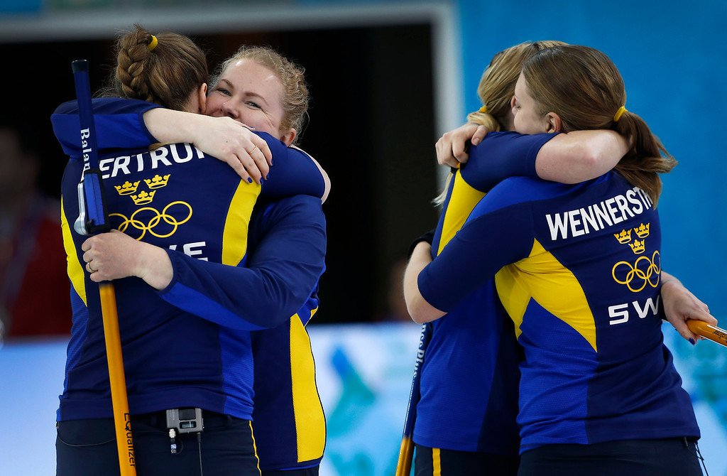 . Sweden\'s women\'s curling team from left to right, Christina Bertrup, left, Margaretha Sigfridsson, Maria Prytz, and Maria Wennerstroem, embrace after beating Russia during the women\'s curling match at the 2014 Winter Olympics, Sunday, Feb. 16, 2014, in Sochi, Russia. (AP Photo/Wong Maye-E)