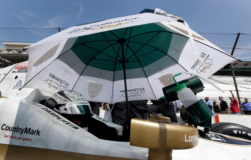 . Ed Carpenter sits in his car under the shade of an umbrella during practice for the Indianapolis 500 auto race at the Indianapolis Motor Speedway in Indianapolis, Thursday, May 16, 2013. (AP Photo/Darron Cummings)
