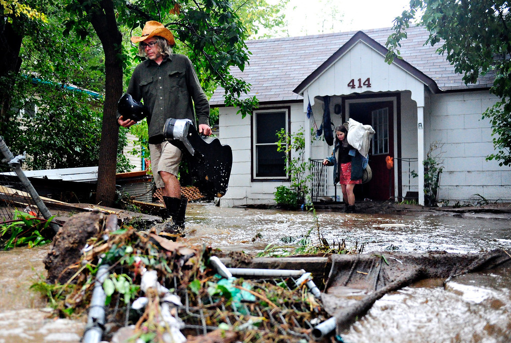 ". Gary McCrumb, left, and Jean Ballhorn wade through flood waters as they carry valuables out of their home, 414 Park Dr., in Lyons Friday, Sept. 13, 2013. McCrumb is planning to stay with friends in town. ""We\'re all taking care of each other,\"" said McCrumb. For more photos visit www.TimesCall.com. (Greg Lindstrom/Times-Call)"