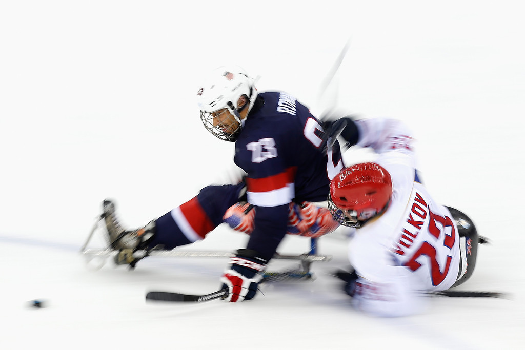 . Roman Rico of USA is tackled by Ilia Volkov of Russia during the Ice Sledge Hockey Preliminary Round Group B match between USA and Russia at the Shayba Arena during day four of the Sochi 2014 Paralympic Winter Games on March 11, 2014 in Sochi, Russia.  (Photo by Harry Engels/Getty Images)
