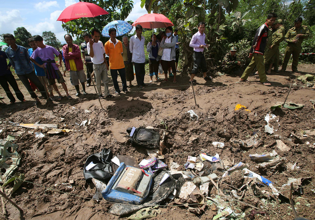 . People look at the debris of a Lao Airlines turboprop plane that crashed into the Mekong River, in Pakse, Laos on Thursday, Oct. 17, 2013. Backpacks, an airplane propeller and passports were among the debris scattered on the riverbank where the Lao Airlines turboprop plane apparently hit hard before skidding into the water and sinking Wednesday, killing all 49 people onboard.  (AP Photo/Sakchai Lalit)