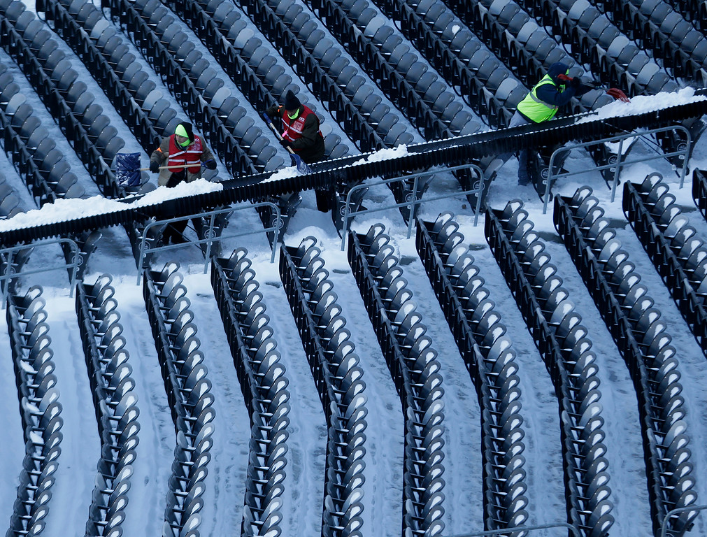 . Workers shovel snow from the seats at MetLife Stadium as crews removed snow ahead of Super Bowl XLVIII following a snow storm, Wednesday, Jan. 22, 2014, in East Rutherford, N.J.  (AP Photo/Julio Cortez)