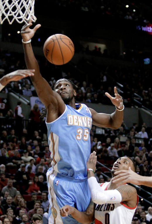 . Denver Nuggets forward Kenneth Faried, left, pulls in a rebound over Portland Trail Blazers guard Damian Lillard during the first half of an NBA basketball game in Portland, Ore., Thursday, Jan. 23, 2014. (AP Photo/Don Ryan)