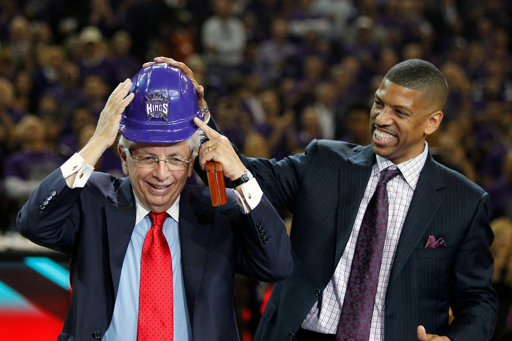 . Sacramento Mayor Kevin Johnson, right, helps NBA Commissioner David Stern put on a hard hat presented to him during ceremonies at the Kings NBA basketball game against the Denver Nuggets in Sacramento, Calif., Wednesday, Oct. 30, 2013. The ceremonies were held to celebrate the purchase of the team by Vivek Ranadive. (AP Photo/Genevieve Ross)